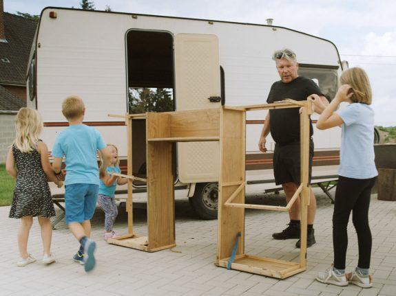 Adulte et deux enfants travaillant sur le cadre en bois d'une caravane.