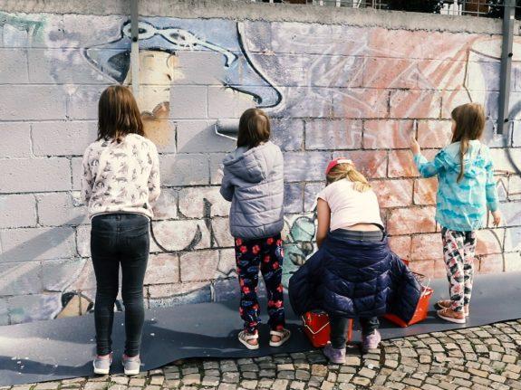 Des enfants peignent en blanc un vieux mur.